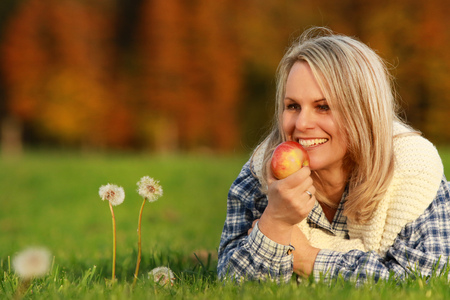Happy mature woman with an apple lying in the meadow in autumn Reklamní fotografie