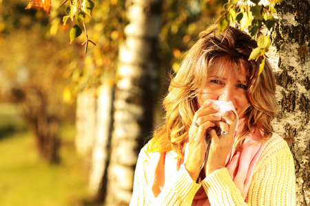 Middle aged woman sneezes with handkerchief outdoor