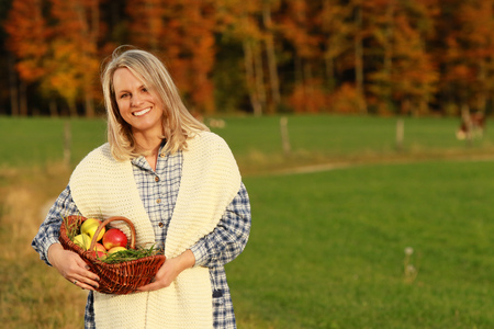Mature peasant woman with a basket with apples and scarf standing outdoor in the countyside