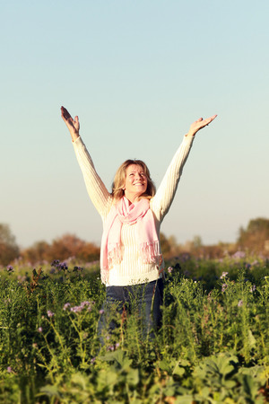 Happy mature woman with scarf and Pullover raising up her arms in a flower field Stock Photo