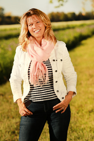 Happy mature woman standing relaxed in the countryside