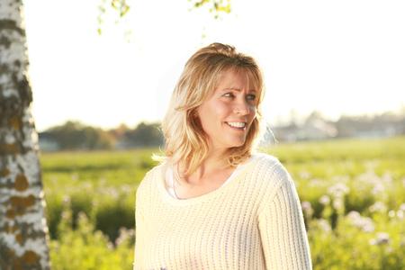 Happy mature woman looking backwards Stock Photo