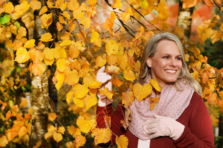 portrait of an attractive middle age woman with scarf and gloves  with yellow autumn leaves in the background