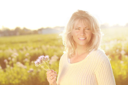 Happy mature woman holding a flower and looking at camera in backlighting Zdjęcie Seryjne