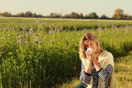 Mature woman sitting in the grass in front of a flowfield, blowing her nose