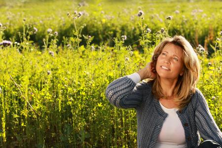 Vrouw van middelbare leeftijd in haar vrije tijd met hand in haar haar zittend voor een bloemenveld Stockfoto