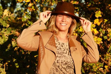 Happy mature woman enjoys the sunny autumn weather Reklamní fotografie