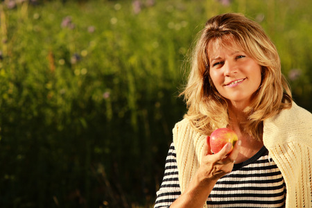 Happy mature woman sitting in the meadow while eating an apple