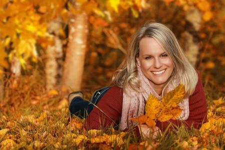 Happy middle age woman lying in the meadow with autumn leaves Reklamní fotografie