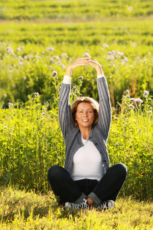 Happy middle aged woman stretching her arms out while sitting in the meadow Reklamní fotografie