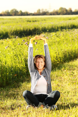 Happy middle aged woman stretching her arms out while sitting in the meadow Stock Photo