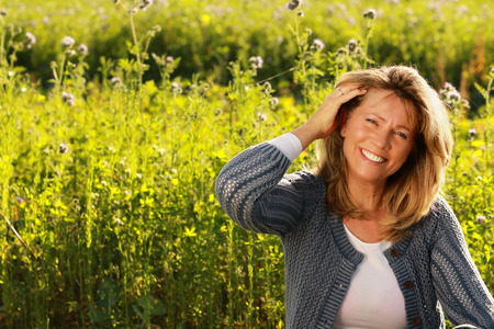 Middle age woman in her leisure time with hand in her hair sitting in front of a flowerfield