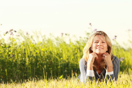 Happy middle age woman with her head on the hands relaxing in the meadow Stock Photo