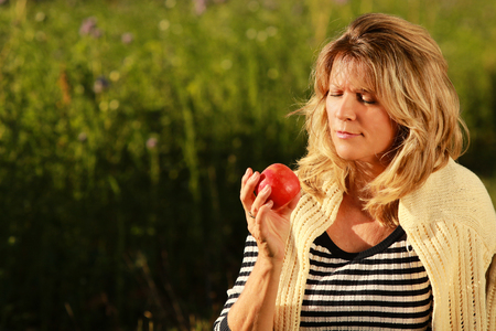 Happy mature woman sitting in the meadow while looking at an apple