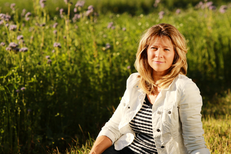 Smiling mature woman relaxes in the grass on a sunny day looking at camera