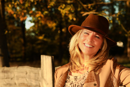 Attractive middleade woman with brown hat smiles in the countryside