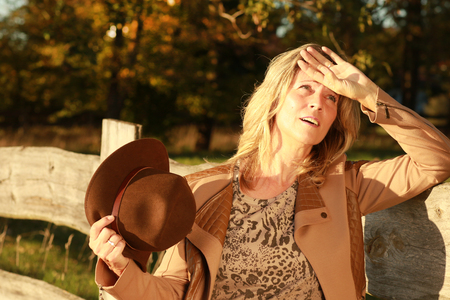 Mature woman tries to get some fresh air in the sun, while moving her hat outdoor