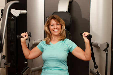 Middle age woman using weight lifter for her arms