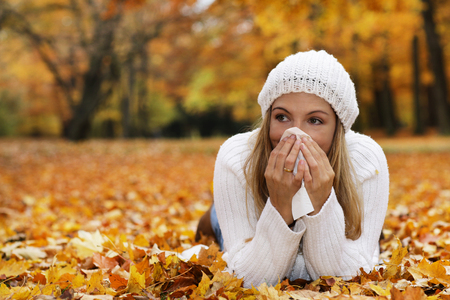 Middle age woman blowing her nose , lying in autumn leaves