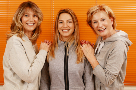 Three happy mature woman with different age together in front of an orange background