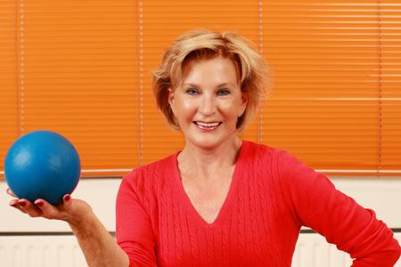 Elderly happy woman holding a blue gymnastic ball