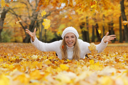 Happy middle age woman throwing yellow autumn leaves while lying on theground