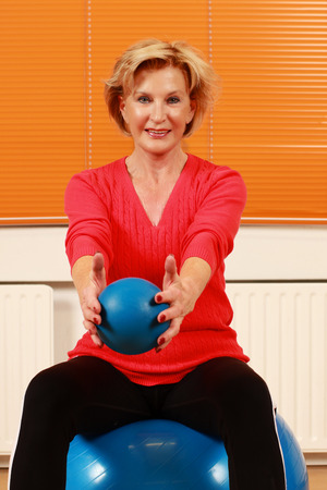 Female pensioner doing sports on a big blue ball