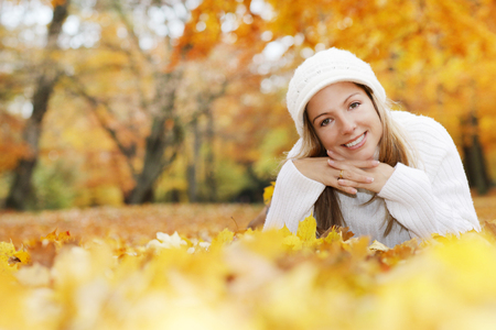 Happy middle age woman with scarf and cap relaxing in the autumn nature while lying on the ground