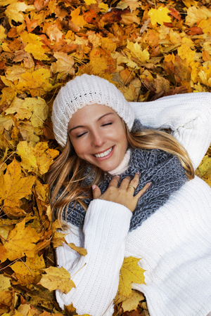 Attractive woman with scarf and cap lying in yellow autumn leaves and looking up
