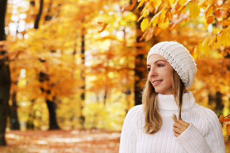 Happy woman in autumn  in profile with autumn background