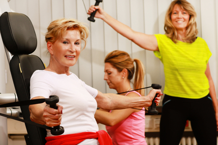 Mature woman in the gym trains her arms with a weight lifter