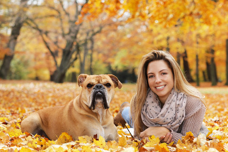 Woman with dog lying on autumn leaves in nature