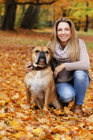 Happy woman with her dog sitting in autumn leaves in nature