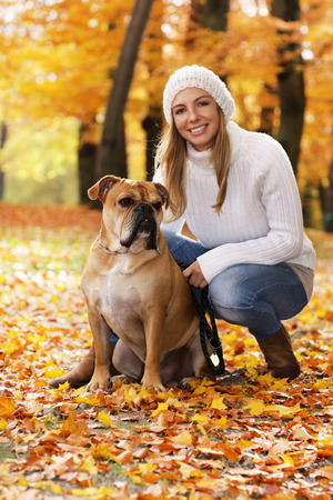 Attractive middle age woman sitting in autumn leaves with a dog at her side Reklamní fotografie - 111764128