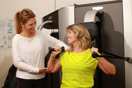 Mature woman with personal female trainer using a weight lifter