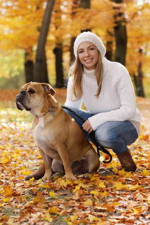 Attractive middle age woman sitting in autumn leaves with a dog at her side