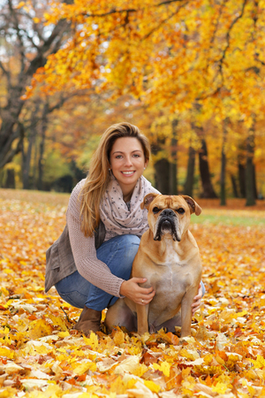 woman and continental bulldog sitting together in nature with autumn leaves