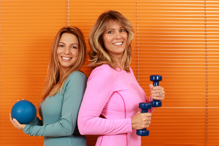 Two woman of different ages with sport equipment in front of orange background