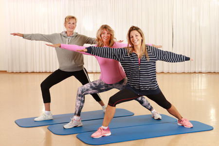 Three woman of different ages doing strtching and power work outs