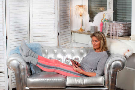 senior woman relaxes with mobile phone on the couch
