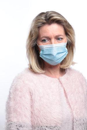 Unhappy senior woman wearing facemask Stock Photo