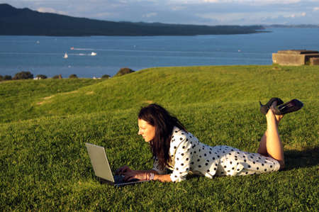 Girl working on laptop outdoors Stock Photo