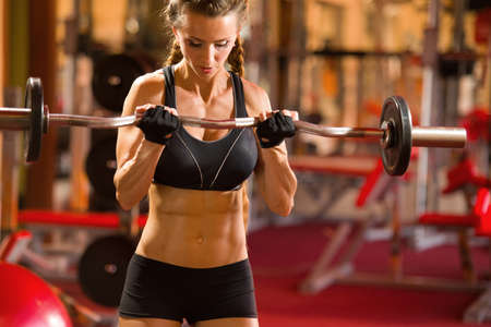 Girl sportswoman trains with a barbell in the gym 版權商用圖片