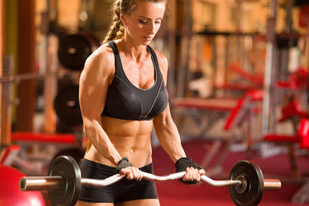 Girl sportswoman doing an exercise with a barbell in the gym