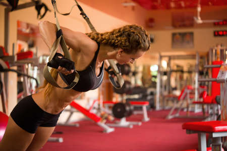 Girl sportswoman trains on the tirex in the gym
