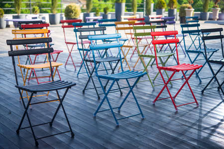 Colored folding chairs for a seminar or training on an open wooden terrace