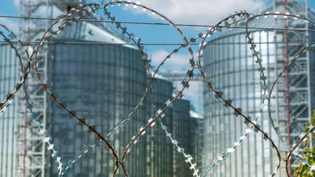 barbed wire fence  elevator cisterns (storage for grain)
