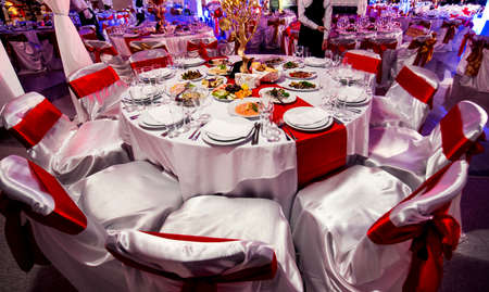 feast on a lot of tables. Table covered with white tablecloth in a restaurant