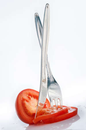 Disposable plastic fork and knife and chopped tomato