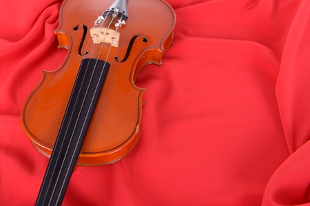 scandals: old violin on on silk fabric. Stock Photo